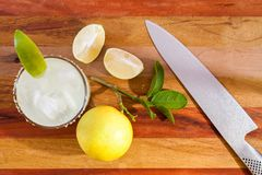 Key lime margarita garnished with fresh lime in a glass bar table knife. view from above Stock Photos