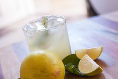 Key lime margarita garnished with fresh lime in a glass bar table Royalty Free Stock Photo
