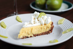 Key Lime Pie on decorated plate. Key Lime Pie dessert on a decorated plate with limes Royalty Free Stock Photo