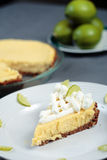 Key Lime Pie on grey cloth with pie and limes in back. Key Lime Pie dessert on a table with pie and limes in the background Royalty Free Stock Photos