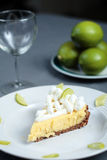 Key Lime Pie on grey cloth with wine glass and limes in back. Key Lime Pie dessert on a table with limes in the background Stock Photo