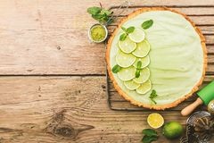 Key Lime Pie. With several limes and mint over wooden background, top view with copy space Stock Images