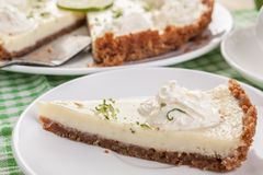Key lime pie. Traditional key lime pie decorated with whipped cream and lime zest on a dish Stock Photos