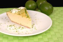 Key lime pie on white plate. With lime zest and limes Royalty Free Stock Photos