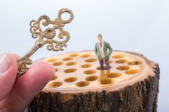 Key and little man figurine places on wooden log royalty free stock images