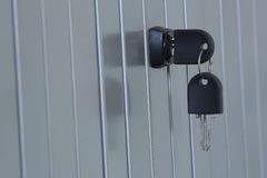 Key in the lock of an office cubicle. This office cubicle has a metal rolling door in it Royalty Free Stock Photo
