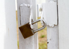 Key lock at white fence for protection asset. Royalty Free Stock Images
