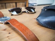 Key male belongings such as a watch and sunglasses. On a wooden table Royalty Free Stock Photo
