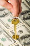 Key and money. Hand holding a golden key over dollar background Stock Photo