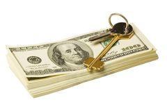 Key and money. Stacks of $100 dollar bills with gold key Royalty Free Stock Photos