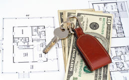 Key and money on home plan Royalty Free Stock Image
