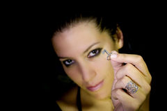 Key of my heart. Beautiful brunette offering silver key (focus on key, girl blurred), isolated on black Royalty Free Stock Image