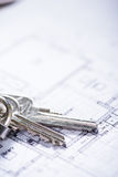 Key for new house on architect drawings Stock Photography