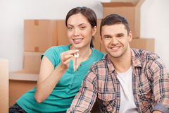 Key of new house. Beautiful young couple sitting close to each other and smiling while holding key from the house Stock Photo