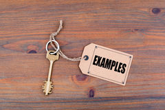 Key and a note on a wooden table with text: Examples.  Royalty Free Stock Photos