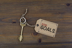Key and a note on a wooden table with text - 2016 goals. New Yea Royalty Free Stock Photos
