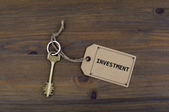 Key and a note on a wooden table with text - Investment Royalty Free Stock Images
