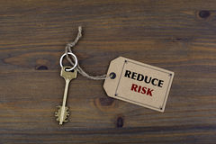 Key and a note on a wooden table with text - REDUCE RISK Royalty Free Stock Images
