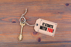 Key and a note on a wooden table with text - It Starts With You Royalty Free Stock Image