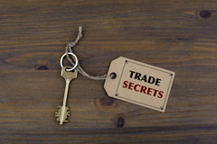 Key and a note on a wooden table with text - TRADE  SECRETS Stock Images
