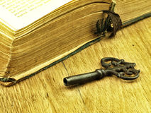 Key and old, open book with a damaged cover. Royalty Free Stock Photography
