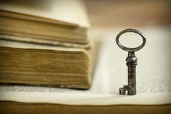 Key on an open old book Royalty Free Stock Photos