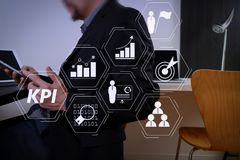 Businessman working with smart phone and digital tablet and lapt. Key Performance Indicator (KPI) workinng with Business Intelligence (BI) metrics to measure Royalty Free Stock Image