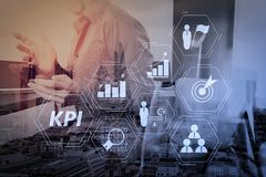 Businessman working with smart phone and digital tablet and lapt. Key Performance Indicator (KPI) workinng with Business Intelligence (BI) metrics to measure Royalty Free Stock Photo