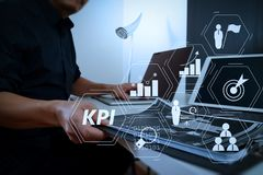 Businessman working with smart phone and digital tablet and lapt. Key Performance Indicator (KPI) workinng with Business Intelligence (BI) metrics to measure Stock Photo