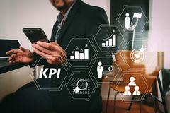Businessman working with smart phone and digital tablet and lapt. Key Performance Indicator (KPI) workinng with Business Intelligence (BI) metrics to measure Stock Photos