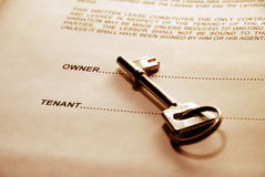 Key on Property Lease. Silver key lying on a property lease document Royalty Free Stock Photography