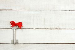 Key with red bow silk ribbon Royalty Free Stock Photography