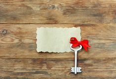 Key with red bow silk ribbon, on wooden table Stock Photos