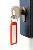 Key with red tag. White door locked with the key in the keyhole and a red tag attached Royalty Free Stock Photography