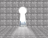 Key shape door on puzzles wall with city view outside Royalty Free Stock Photos