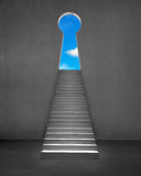 Key shape door on wall with stairs and blue sky Stock Photos