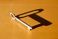 Key with sharp shadow. Classic key with sharp shadow on wooden surface Royalty Free Stock Photo