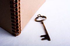 Key and spiral notebook. Key by the side of a  spiral notebook on a white background Royalty Free Stock Images