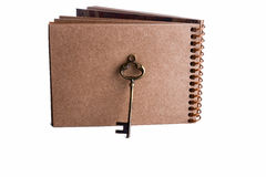 Key and spiral notebook. Key by the side of a  spiral notebook on a white background Stock Photos