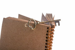 Key and spiral notebook. Key on the top of a  spiral notebook on a white background Stock Photography
