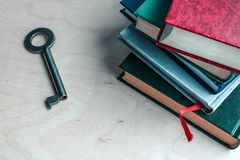 Key and stack of books on wooden background. Metaphor - key to knowledge stock images