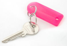 Key and Tag. A house key on a pink tag Royalty Free Stock Image