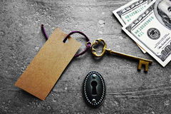 Key tag and cash. Gold key with blank tag, with keyhole and cash Royalty Free Stock Image