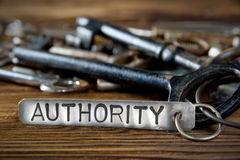 Key Tag Concept. Photo of key bunch on wooden board and tag with letters imprinted on clean metal surface; concept of AUTHORITY Royalty Free Stock Images