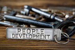 Key Tag Concept. Photo of key bunch on wooden board and tag with letters imprinted on clean metal surface; concept of PEOPLE DEVELOPMENT Stock Image