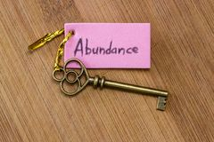 Key to abundance. Concept image using a key and a tag with the word abundance handwritten on it over a wooden background royalty free stock photos