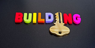 Key to building. Text ' building ' in colorful uppercase letters with a gold key replacing the letter ' i ' and isolated on a dark background, concept making Royalty Free Stock Photos