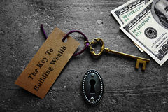 Key to building wealth. With keyhole and money Stock Photo