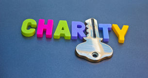 Key to charity. Text 'charity' in colorful uppercase letters with letter 'i' replaced with gold key. Concept of raising money for charity or obtaining help from Stock Image