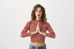 Key is to find peace in yourself. Portrait of cute caucasian female holding hands in pray or standing in meditating pose. Wearing red lipstick and cropped top Royalty Free Stock Photo